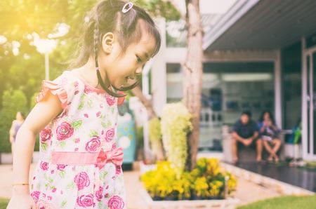 niños saliendo de la escuela: Niño asiático que juega en el patio de la escuela con los padres en el fondo. Foto de archivo