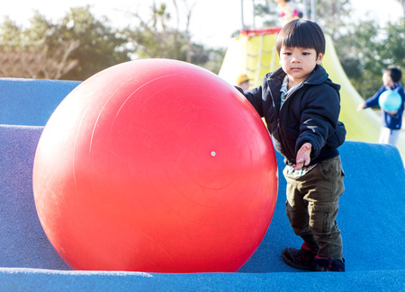 rubber ball: Asian boy is playing with big rubber ball