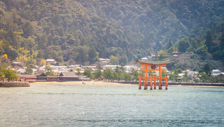 social history: Hiroshima, Japan - March 16, 2016: The famous Orange Torii gate is located in the beach of Miyajima Island.