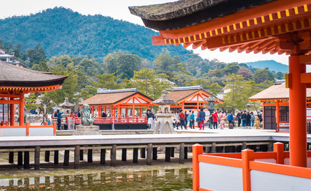 social history: Hiroshima, Japan - March 16, 2016: Tourists are taking picture of Miyajima Torii from the corridor of the floating temple.