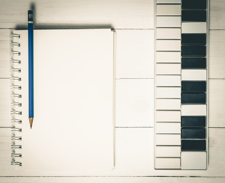 Music Keyboard with blank note book for song writing. Stock Photo