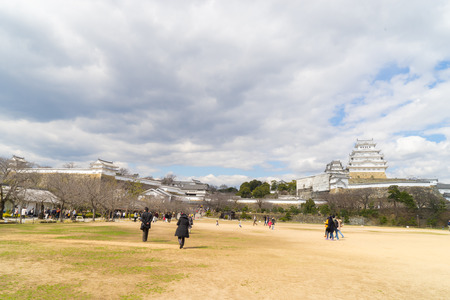 social history: Himeji, Japan - March 12, 2016: Tourist are walking to Himeji castle through the front garden.