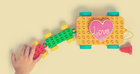 toy block: a children hand pulling colorful love train toy block Stock Photo
