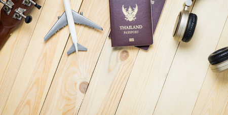 plane table: Travel objects equipments on wooden table with copy space. Travel Banner with passport, plane, headphone for summer music vacation travel. Stock Photo