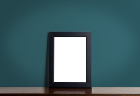 room accents: Blank photo frame on wooden table with navy wall background.