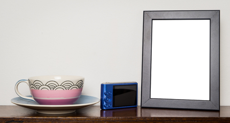 room accents: Blank photo frame on wooden tablet with tea cup and camera Stock Photo