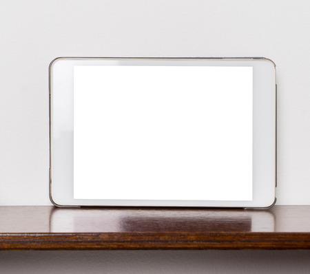 bookshelf digital: Blank White tablet screen on wooden shelf with white wall.