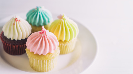 Colorful pastel cup cake muffins on white background