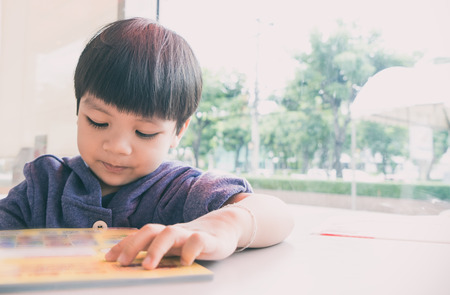 3 year old: Asian 3 year old boy is reading picture book with copy space. Stock Photo