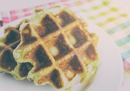 honey tone: Baked golden honey waffles on white plate in vintage tone. Stock Photo