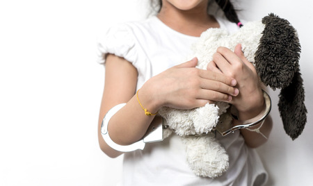 handcuffed: Child holding a doll with her hand in handcuffed copy space Stock Photo
