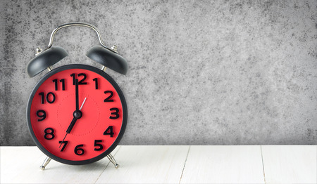 second breakfast: Red Alarm clock on white table with concrete wall