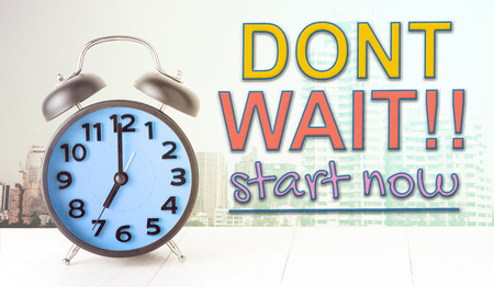 react: Dont wait start now text with blue alarm clock Stock Photo