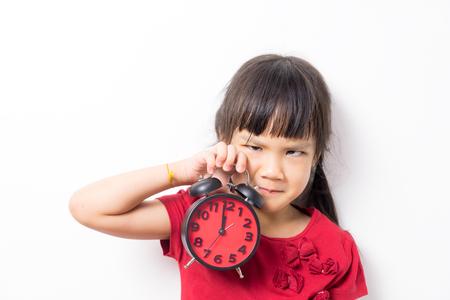 Asia niña está enojado y con ganas de ir a la cama. Muchacha que sostiene un reloj contando a la media noche de solicitar tiempo de la cama. Sleepy niña cansada necesita ir la cama a dormir.