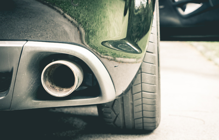 exhaust gases: Luxury Sport car muffler on the right hand side. Stock Photo