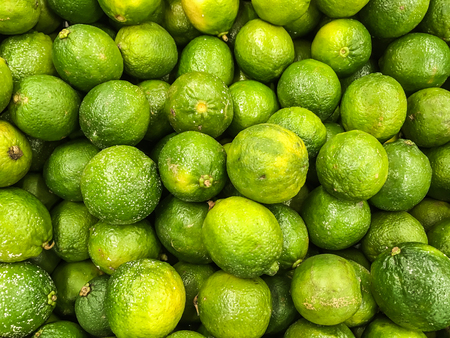 A large group of Thai green orange on sale in the market. This orange are grown in Thailand. Unlike most of imported orange, these Thai orange are much sweet and smaller. Stock Photo