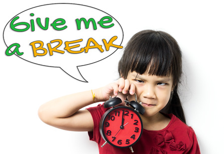 give out: Angry Asian baby girl is holding a clock asking for a lunch break. An unhappy little girl telling you to Give Me a Break. Asian Student is stressed out and asking for a Break. Stock Photo