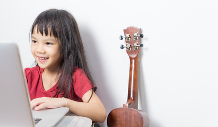 learning computer: Little musician kid is working on her music on a laptop. Asian kid is looking for music note on the Internet. Japanese girl is taking a guitar music course online.