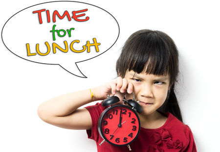 reminding: Asian little kid is holding the clock reminding you she need to go for lunch.