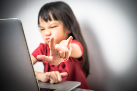 Asian girl showing Love or heavy metal sign hand while using the laptop computer surfing the Internet.