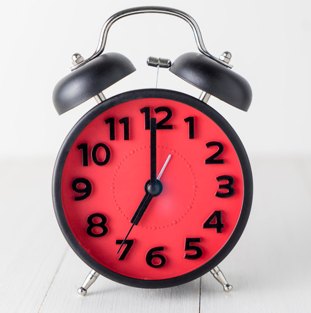 Red Alarm Clock on white wooden tablet setting up at 7