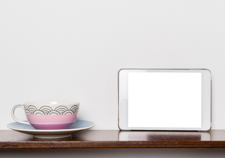blank tablet: Pastel Tea cup with Blank white tablet screen. Stock Photo