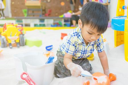 少年は、教育の遊び場の砂場のおもちゃで遊んでいます。この細かい砂は特に清潔で作られた子供の遊び場のため。