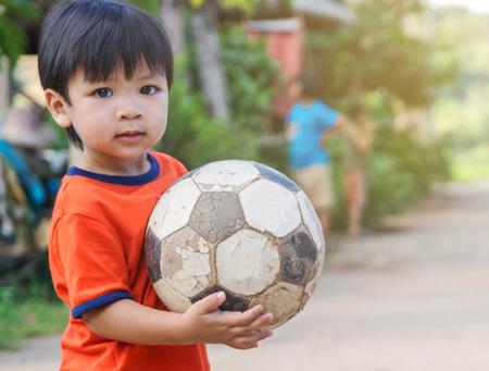 Asia niño en el pueblo pobre que juega con el viejo balón de fútbol