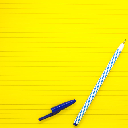 yellow study paper with blue pen ready to write, copy space for your text. Stock Photo