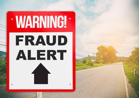 road ahead: Fraud Alert ahead warning signage on the road ahead. Stock Photo