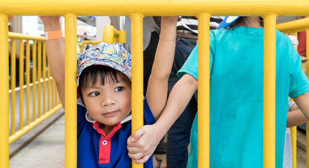 Little Asian boy hanging on a metal fence. Stock Photo