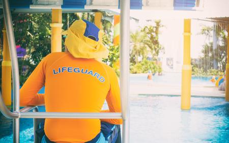gaurd: Life gaurd stting on a twoer in swimming pool Stock Photo