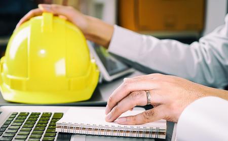 L'ingegnere edile sta leggendo le istruzioni sul suo taccuino Archivio Fotografico - 73492895