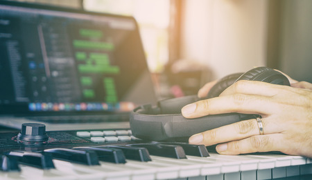 daw: Musician holding a Headphone on music keyboard in home mmsuic studio Stock Photo