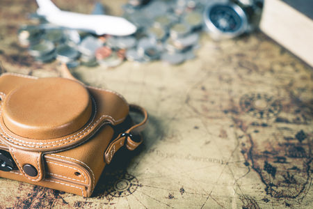 map case: Leather camera case and traveler equipment on vintage map
