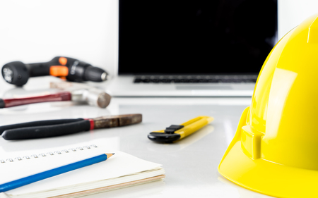 Repairman construction helment and screwdriver with computer Stock Photo