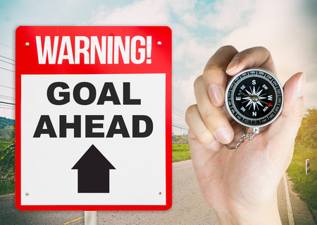 succession planning: Warning sign goal ahead with hand holding compass for direction Stock Photo
