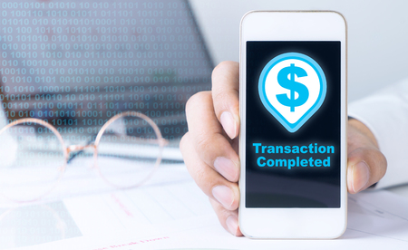 Business man is holding smartphone with transaction complete icon Фото со стока
