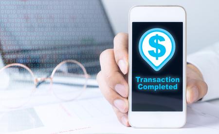 Homme d'affaires tient un smartphone avec une icône complète de transaction Banque d'images