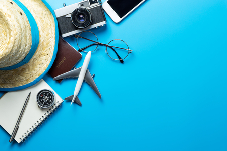 Travel accessories with copy space on blue background Foto de archivo