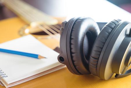 Songwriterapparatuur met hoofdtelefoon en notitieboekje op gitaar