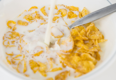 pouring milk into Corn flake cereal breakfast