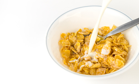 Pouring Milk into corn flake breakfast cereal bowl