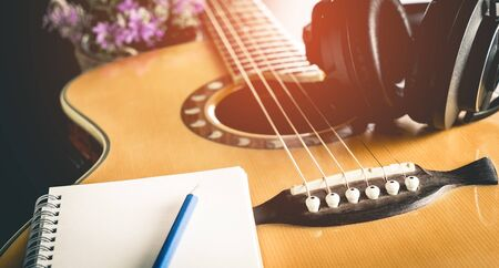 Song writer guitar and headphone with empty book for composer