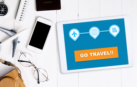 "Online reiswebsite op tablet ""Go travel"" -knop met reisaccessoires Stockfoto"