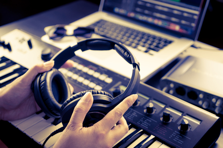 Sound Engineer is picking headphone to start mixing song. Stock Photo - 78745791
