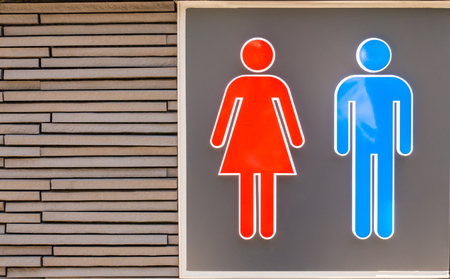 Male and Female Restroom signage on brick wall