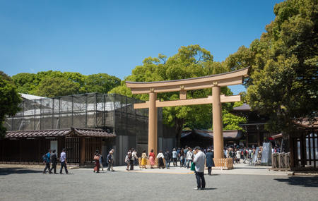 Tokyo, Japan - May 5, 2017: Tourists are entering the Meiji Shrine through the wooden gate.
