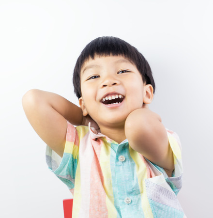 Lively Asian boy is laughing happily on white background. Stock fotó