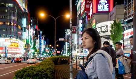 Tokyo, Japan - May 5, 2017: A girl is crossing Shinjuku shopping street.